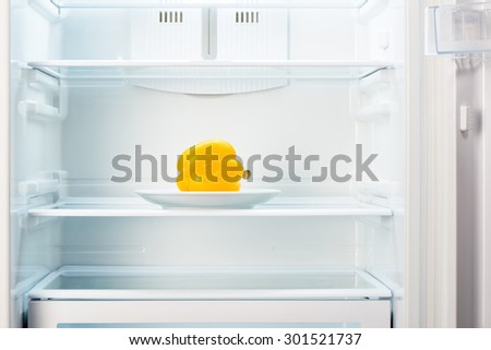 Yellow pepper on white plate in open empty refrigerator. Weight loss diet concept.  - stock photo