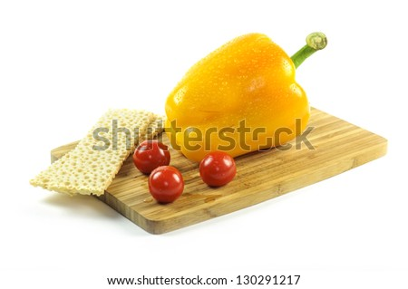 Yellow pepper with tomatoes and crisps on the wooden cutting board - stock photo