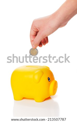 Yellow piggy bank is getting two euro coin from a hand on white background - stock photo