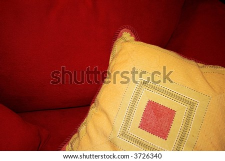 yellow pillow on a red couch - stock photo