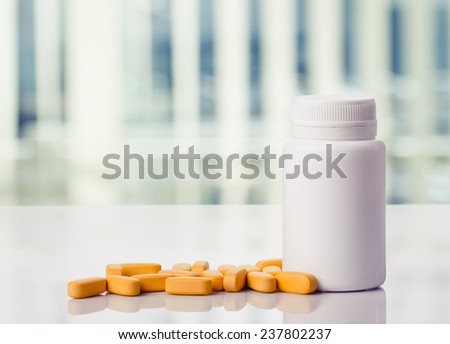 Yellow pills and pills bottle on a white table,toned photo. - stock photo