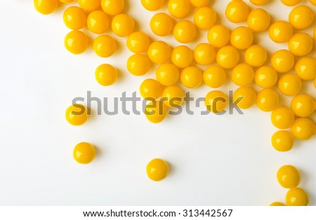 Yellow pills are spilled on the white surface. Vitamins. - stock photo