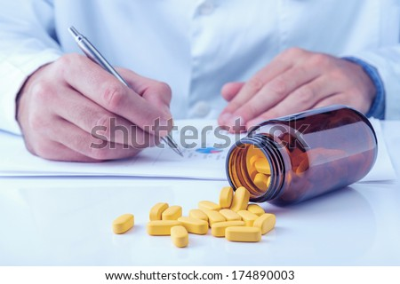 Yellow pills on table, doctor writing medical note. Toned photo - stock photo