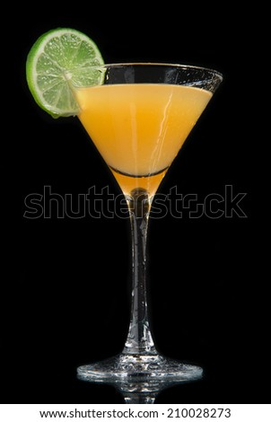 Yellow pineapple cocktail decorated with lime in martini cocktails glass isolated on a black background - stock photo
