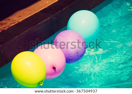 yellow pink blue and purple balloons float in water pool - stock photo