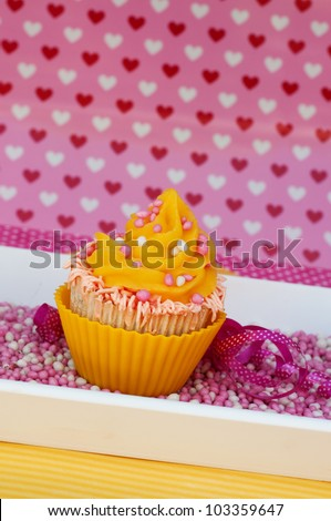 Yellow pink cupcake on a plateau with rusk and hearts background - stock photo