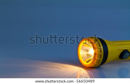 yellow plastic pocket flash-light - stock photo