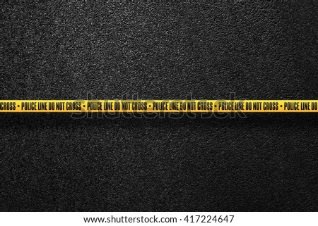 Yellow police line in the background smooth asphalt road. Police line do not cross. The texture of the tarmac, top view. - stock photo