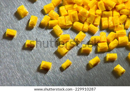 yellow polymer pellets on stainless steel sheet  - stock photo