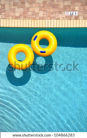 Yellow pool float, pool ring in cool blue refreshing blue pool, room for your text - stock photo