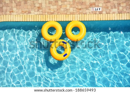Yellow pool rings floating in a swimming pool - stock photo