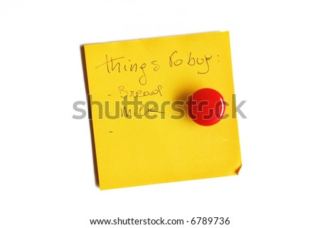 Yellow post-it isolated on white with round red magnet and handwritten message - stock photo