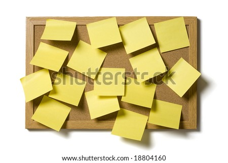 Yellow post it notes covering a cork board, isolated on a white background - stock photo