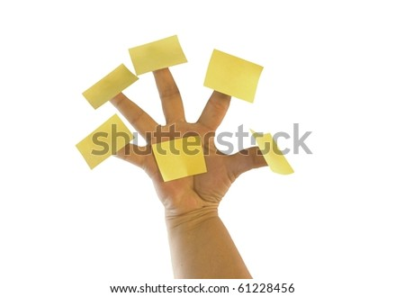 Yellow post notes on fingers of a female hand - stock photo
