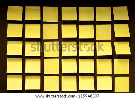 Yellow post notes 5x7 rows covering a cork board - stock photo