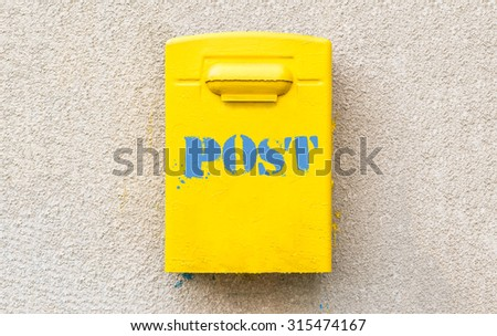 Yellow post office mailbox with label on plastered wall. - stock photo