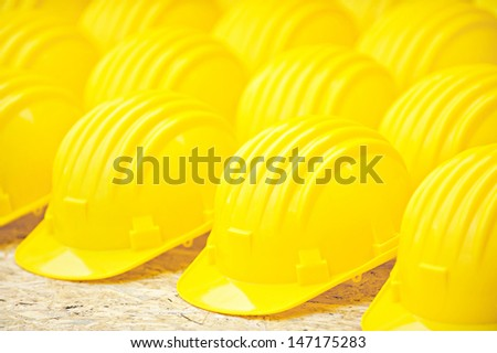 Yellow protection helmets in a row - stock photo