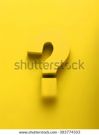 Yellow question mark on a vibrant colorful yellow background with feint shadow and copy space in a conceptual image - stock photo