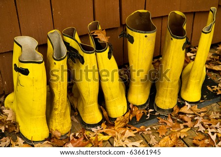 Yellow rain boots lined up on the deck on a fall day - stock photo