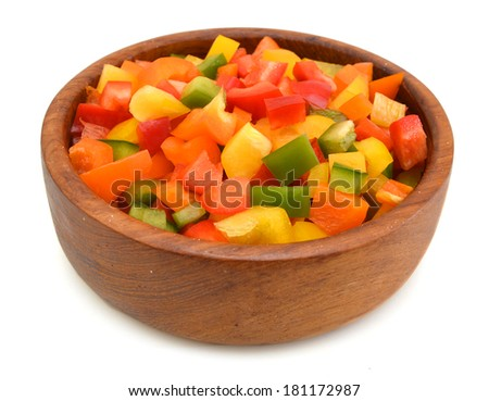 Yellow, red and green peppers Bulgarian. Slicing. Cubes in wooden bowl on white  - stock photo