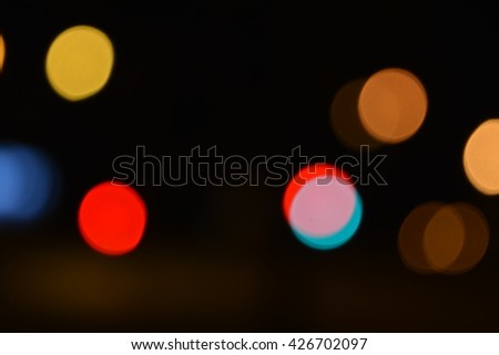 Yellow, red, blue, brown defocused blurry circular night city lights glowing soft in the darkness with bright colors. They soothe, brings a positive and evenly distributed on the photo. - stock photo