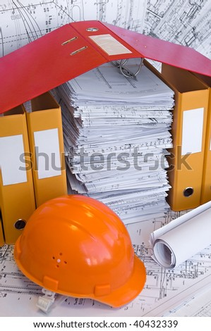 Yellow, red file folders, helmet and heap of design drawings are on the table. Business still-life. - stock photo