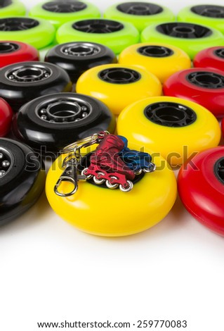 Yellow, red, green and black inline skate wheels and keychain in the shape of roller shoes - stock photo