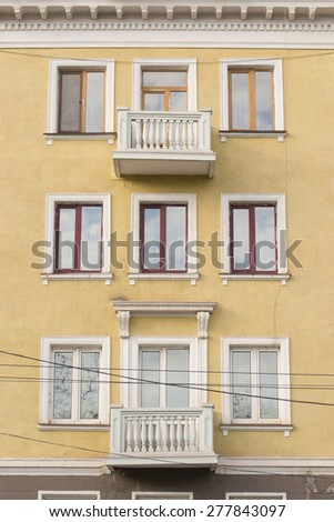 Yellow residential house facade with balcony, cables - stock photo