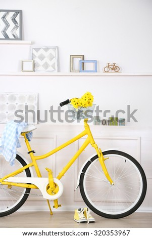 Yellow retro bicycle in spacious bright room - stock photo