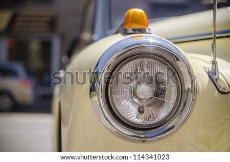 Yellow retro car headlight close-up - stock photo