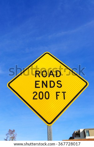 Yellow road ends ahead in 200 feet road sign with black lettering against blue sky. - stock photo