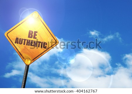 Yellow road sign with a blue sky and white clouds: be authentic - stock photo