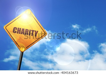 Yellow road sign with a blue sky and white clouds: charity - stock photo