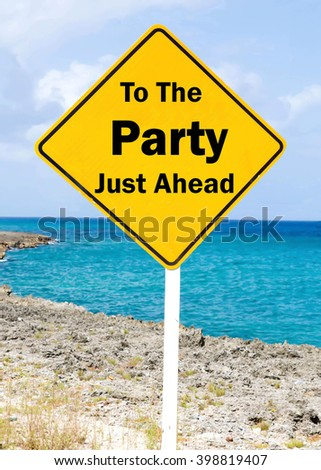 Yellow road sign with a To The Party Just Ahead concept against a coastal setting with a partly cloudy sky background. - stock photo