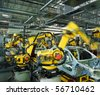 yellow robots welding cars in a production line - stock photo