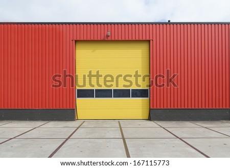 yellow roller door in an orange building - stock photo