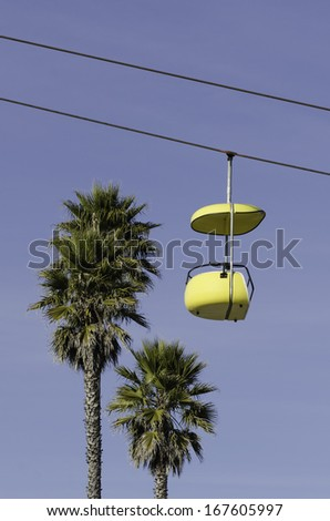 Yellow Ropeway surrounded by palms - stock photo