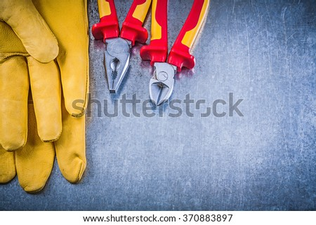 Yellow safety gloves pliers wire-cutter on metallic background electricity concept. - stock photo