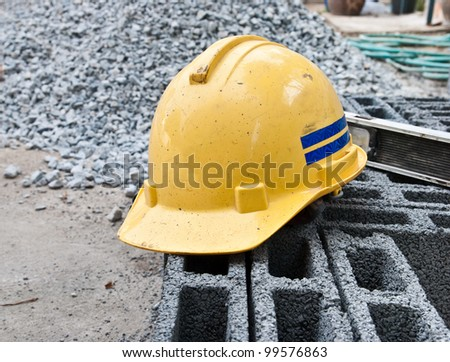 Yellow safety hard hat putting over bricks on construction site - stock photo