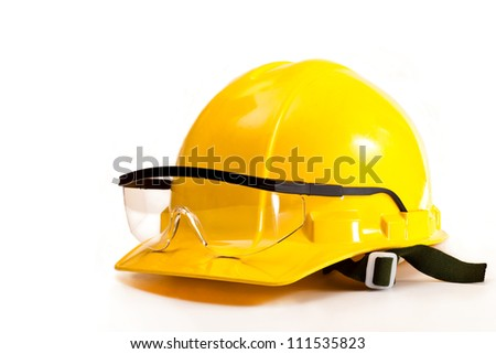 Yellow safety helmet and goggles on white background - stock photo