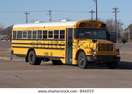 Yellow school bus in a parking lot - stock photo