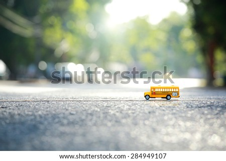 Yellow school bus toy model the road crossing.Shallow depth of field composition and  afternoon scene. - stock photo
