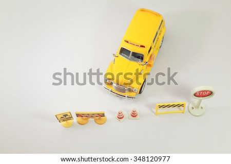 Yellow school bus ( toy model ) with traffic signs. - stock photo