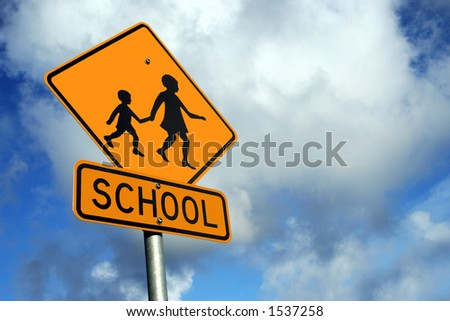 Yellow school road sign against a blue cloudy sky - stock photo