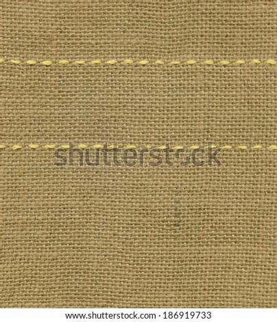 Yellow seam on sack background - stock photo