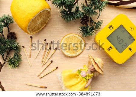 Yellow set of lemon, clock, small toy doll and matchsticks surrounded by green pine tree branches. - stock photo