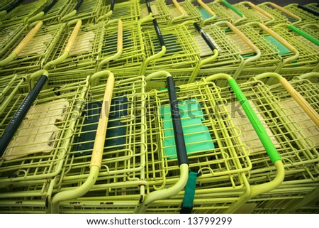 yellow shopping carts in a parking lot - stock photo