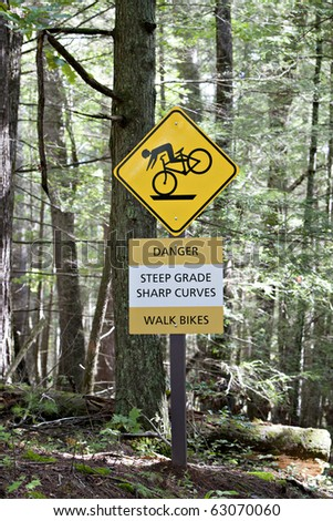 Yellow sign in forest showing  bicyclist and indicating Danger, steep grade, sharp curves, walk bikes - stock photo