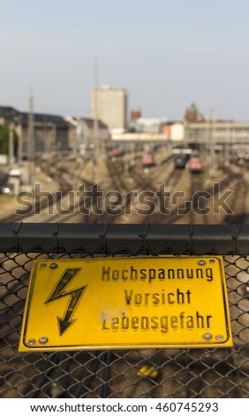 Yellow sign warning for high voltage contact wires above the rails - stock photo