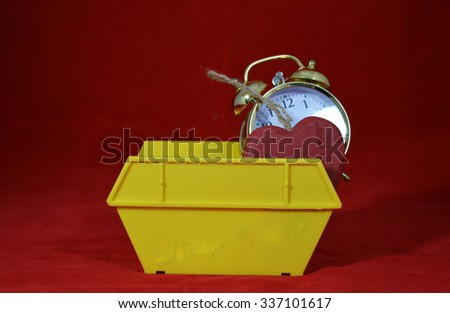 Yellow Skip with alarm clock and dumped heart - stock photo